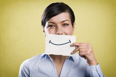 Smiling businesswoman holding blank white card in front of her mouth. Royalty Free Stock Images