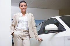 Smiling businesswoman holding a car door handles Stock Photo