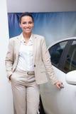 Smiling businesswoman holding a car door handles Stock Photos