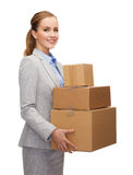 Smiling businesswoman holding cardboard boxes Royalty Free Stock Photos