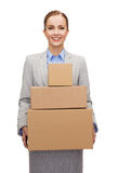 Smiling businesswoman holding cardboard boxes Royalty Free Stock Image