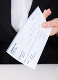 Smiling businesswoman holding cheque Royalty Free Stock Image