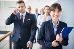 Smiling Businesswoman Holding Clipboard While Walking With Team. Portrait of smiling businesswoman holding clipboard while walking with team in office Royalty Free Stock Photo