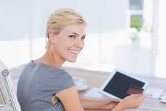 Smiling businesswoman holding credit card and tablet Stock Photos