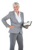 Smiling businesswoman holding diary with her hand on hip Stock Photos