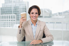 Smiling businesswoman holding disposable cup at her desk Royalty Free Stock Photography