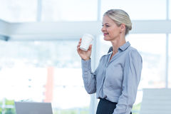 Smiling businesswoman holding disposable cup Royalty Free Stock Images