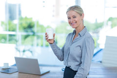 Smiling businesswoman holding disposable cup Royalty Free Stock Image