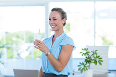 Smiling businesswoman holding disposable cup Stock Images