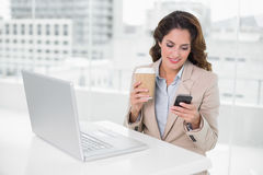 Smiling businesswoman holding disposable cup and smartphone Royalty Free Stock Photography