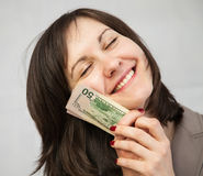 Smiling businesswoman holding dollars. Neutral background Royalty Free Stock Photography