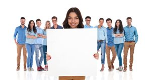 Smiling businesswoman holding empty board in front of her group stock image