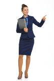Smiling businesswoman holding file and pointing into distance. A successful businesswoman points to her completed project, explaining what it is all about. In Stock Photos