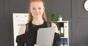 Smiling businesswoman holding a file. Portrait of happy businesswoman holding a file at office stock footage