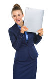 Smiling businesswoman holding file up next to face Stock Image