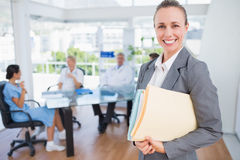 Smiling businesswoman holding files and looking at camera Royalty Free Stock Photos