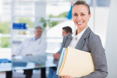 Smiling businesswoman holding files and looking at camera Royalty Free Stock Photo