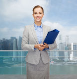 Smiling businesswoman holding folder over city Stock Image