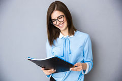 Smiling businesswoman holding folders over gray background Stock Photos