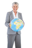 Smiling businesswoman holding globe Stock Photo