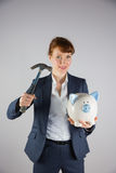 Smiling businesswoman holding hammer and piggy bank Royalty Free Stock Image