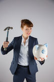 Smiling businesswoman holding hammer and piggy bank Stock Photo
