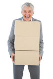 Smiling businesswoman holding heavy cardboard boxes Royalty Free Stock Images