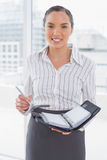 Smiling businesswoman holding her appointment calendar Royalty Free Stock Photos