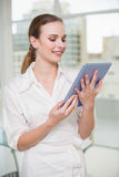 Smiling businesswoman holding her tablet pc Royalty Free Stock Images