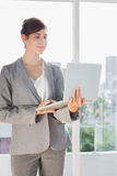 Smiling businesswoman holding laptop and standing Stock Images