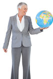 Smiling businesswoman holding and looking at globe Stock Images