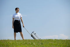 Smiling businesswoman holding luggage in park Stock Images