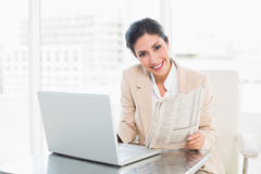 Smiling businesswoman holding newspaper while working on laptop Royalty Free Stock Photography