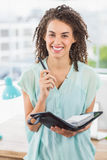 Smiling businesswoman holding a notebook and pen Stock Photography