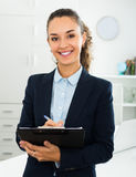 Smiling businesswoman holding pad with documents stock photography
