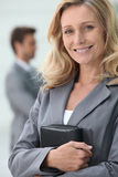 Smiling businesswoman. Holding personal organiser with colleague in background Royalty Free Stock Image