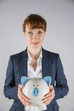 Smiling businesswoman holding piggy bank Royalty Free Stock Photos