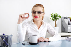 Smiling businesswoman holding a pill. Stock Image