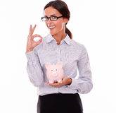 Smiling businesswoman holding pink piggy bank Stock Images