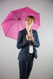 Smiling businesswoman holding pink umbrella Stock Photo