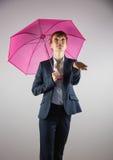 Smiling businesswoman holding pink umbrella Stock Image
