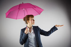 Smiling businesswoman holding pink umbrella Stock Photography