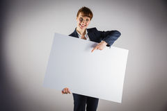 Smiling businesswoman holding and pointing to poster Stock Photos