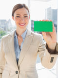 Smiling businesswoman holding up green business card Stock Photos