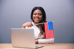 Smiling businesswoman holding US flag Stock Photos