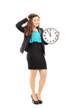 Smiling businesswoman holding a wall clock Royalty Free Stock Photography