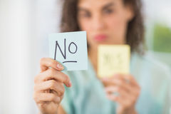Smiling businesswoman holding yes and no sticks. Portrait of a smiling businesswoman holding yes and no sticks Stock Photography
