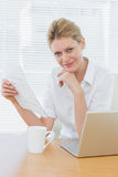 Smiling businesswoman with laptop and document at desk Stock Photo