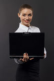 Smiling businesswoman with laptop in studio Royalty Free Stock Images