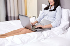 Smiling businesswoman with laptop typing in bed Royalty Free Stock Images